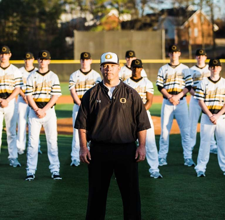 Highschool varsity baseball coach and players posing